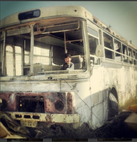 "My 7 year old ""driving"" an abandoned bus on Kibbutz Hannaton"