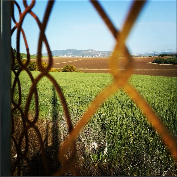 Tel Hannaton through fence, by Jen Maidenberg